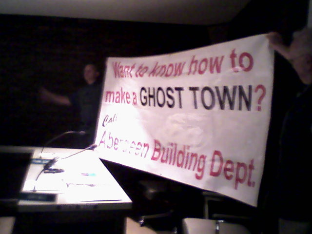 Gordon held up one of the vinyl signs for the council last night