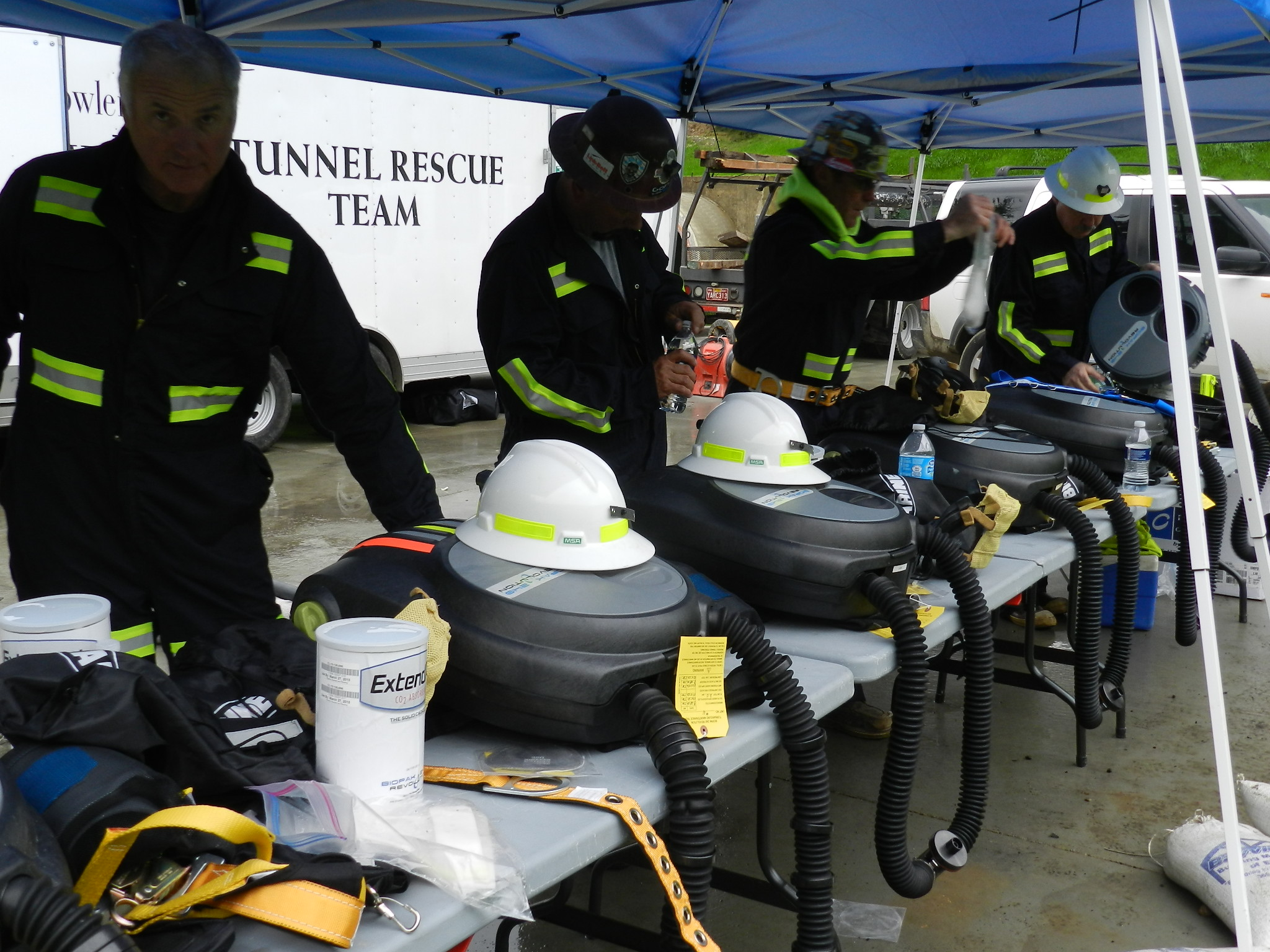 Tim Conley, left, and other members of the James W. Fowler Co. tunnel rescue team meticulously and methodically check their equipment before heading into the smoke-filled tunnel.