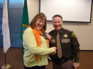 3.Sheriff Casey Salisbury on the right, awarding an appreciation award to Louann Davis on the left.