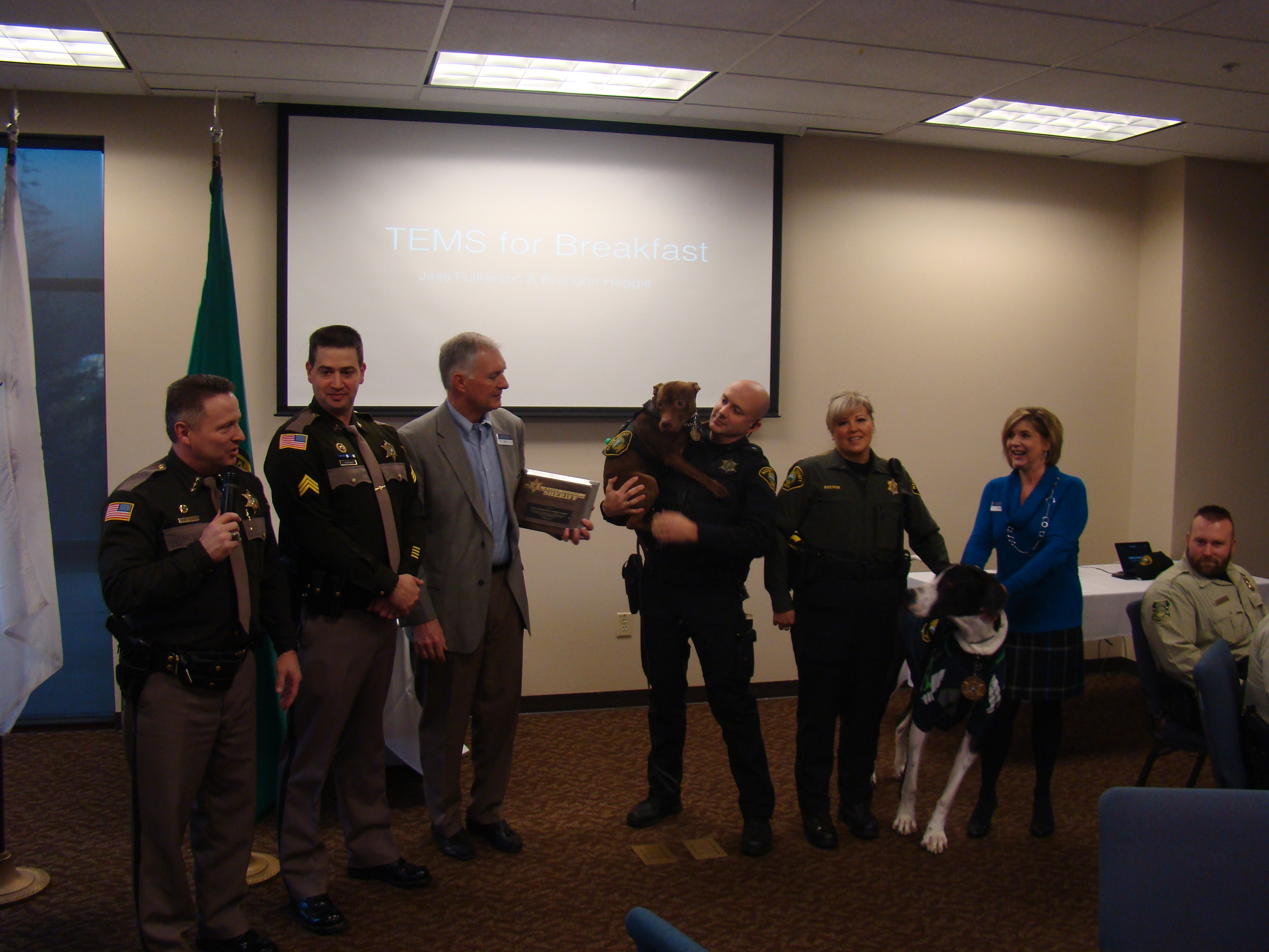 "Group photo of OCCU supporting the K-9 program.  Left to right, Sheriff Casey Salisbury, Sergeant Trevor Severance (K-9 Supervisor), OCCU Bert Fisher, Deputy Sheriff Sean Dodge with K-9 ""Kona"", Animal Control Officer Cindy Brewer with K-9 ""Jack"", and OCCU Daris Devaney."