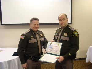 Sheriff Casey Salisbury on the left, awarding Deputy of the Year 2013 to Deputy Sheriff Chris Mondry on the right.