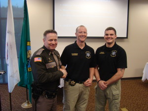Sheriff Casey Salisbury on the left, presenting the Mason County Sheriff's Office Challenge Coin to Paramedic Jess Fulkerson in the middle and Paramedic Brandon Heggie on the right.