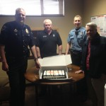 Celebrating with a cake is (left) Chief Jeff Myers, Deputy Chief Don Wertanen, Police Services Officer Jared Spaur and DOC Supervisor Dave Thomson who supervises the community corrections offices in Grays Harbor in Pacific Counties.   And for the record, the prisoners did not partake in the cake.