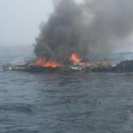 The 25-foot pleasure craft Dawn Trader is engulfed in flames following an engine fire three miles north of Neah Bay, Wash., Aug. 3, 2014.  A Coast Guard MH-65 Dolphin helicopter crew from Air Station Port Angeles safely hoisted the vessel operator from his life raft and transported him to a nearby hospital.   U.S. Coast Guard photo courtesy of Coast Guard Station Neah Bay.