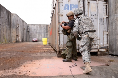 A Soldier with the Washington Army National Guard's 319th Explosive Ordnance Disposal Company, 741st Ordnance Battalion, confers with an officer from the Bellevue Police Bomb Squad, while inspecting a suspected vehicle borne improvised explosive device on a training lane June 26, 2015, at Satsop Regional Educational and Training Center in Elma, Wash., as part of Raven's Challenge IX
