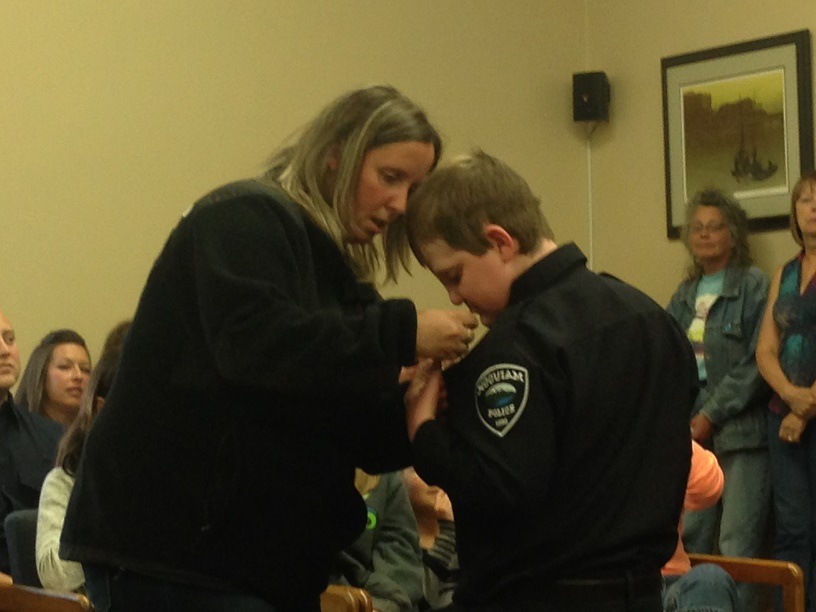 Evan has his new badge pinned to his chest by his mother.