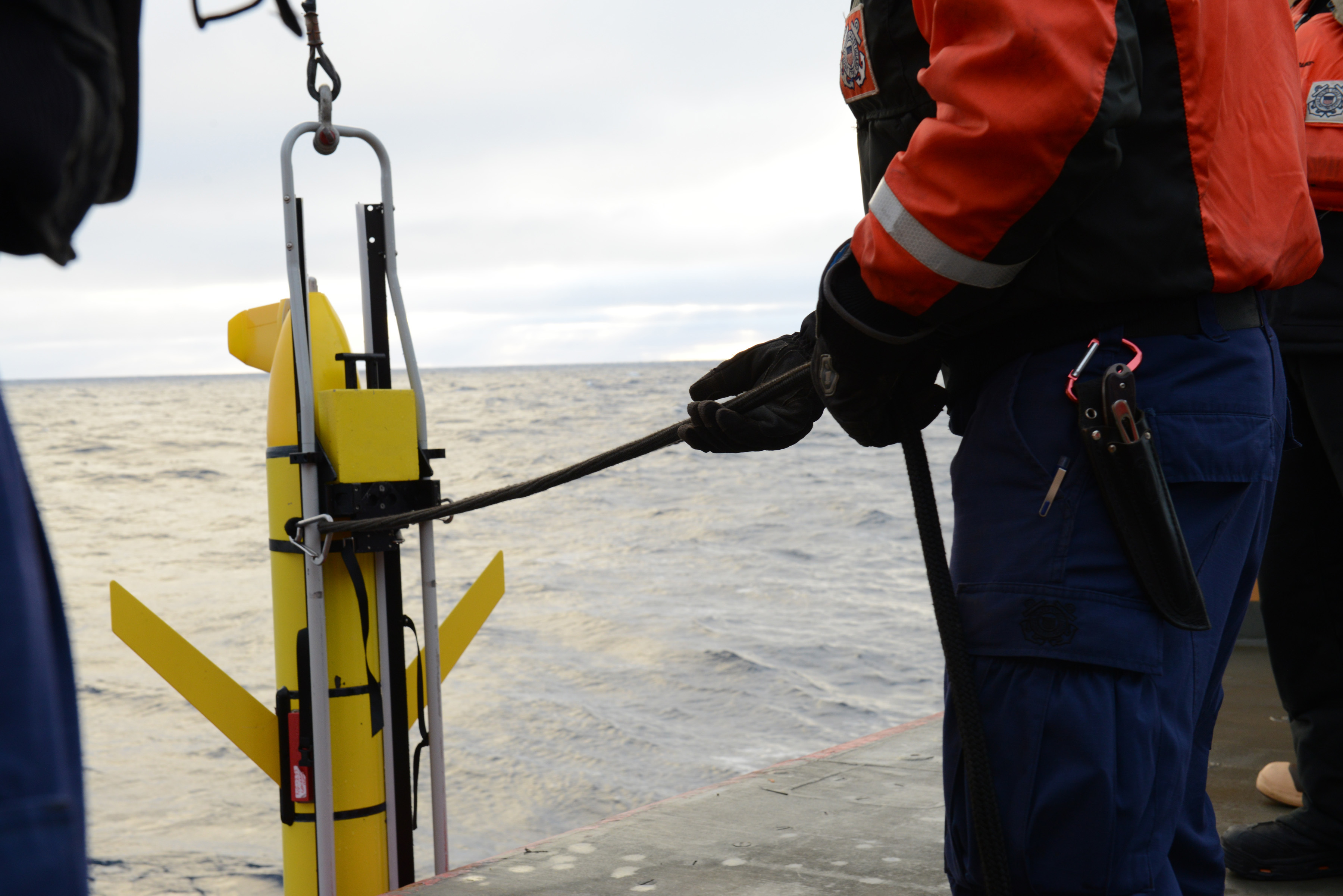 A crewmember aboard Coast Guard Cutter Healy guides a Sea Glider down to the water while transiting the Arctic on Sept. 20, 2016. Scientists aboard the Healy deploy measuring instruments to collect data on the ever-changing Arctic. U.S. Coast Gaurd photo by Petty Officer 3rd Class Lauren Steenson.